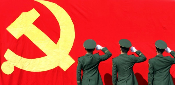 Paramilitary policemen hold their fists in front of a flag of Communist Party of China as they attend an oath-taking rally to ensure the safety of the upcoming 18th National Congress of the Communist Party of China, at a military base in Hangzhou